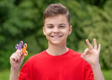 Teen boy with spinner. Young teen boy holding popular fidget spinner toy - outdoors portrait. Happy smiling child making ok gesture and playing with Spinner in Stock Photography