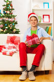 Young teen boy with many presents on the sofa Royalty Free Stock Photo