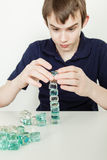 Young Teen Boy Stacking Glass Blocks into Tower stock photo