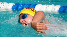 A young teen competes in freestyle swimming. A multi ethnic teen competes in freestyle swimming in an outdoor pool Stock Images