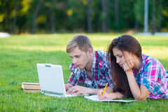 Young teen couple with laptop computer. On the green grass in the park stock image