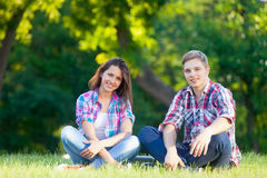 Young teen couple in the park. Young teen couple on the green grass in the park royalty free stock photo