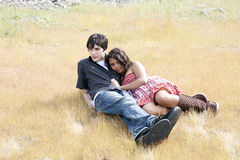 Young teen couple reclining outdoors. Caucasian male and hispanic teen girl outdoors reclining yellow grass Stock Photo
