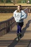 Young Teen Crossing Bridge on Stroller Skates Royalty Free Stock Photo