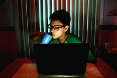 Young Teen drinking coffee in front of a laptop computer Stock Photos