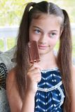 Young Teen Eating Ice Cream. Young girl / child about to eat a chocolate ice cream on a stick Stock Photography