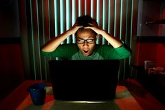 Young Teen with eyeglasses acting surprised in front of a laptop computer. Photo of a Young Teen with eyeglasses acting surprised in front of a laptop computer royalty free stock images