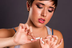 Young Teen Female Just 18 Breaks Cigarette Quits Smoking. A woman so young has already had enough of smoking stock image
