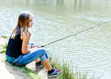 Young teen fishing on a river bank Stock Images