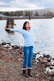 Young teen girl with arms lifted and outstretched, praising God on rocky shore by lake. Young biracial teen girl in blue shirt and jeans, arms lifted and Stock Photo
