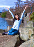 Young teen girl arms raised while sitting on large rock along lake shore, happy. Happy young biracial teen in blue shirt and jeans sitting on large rock by lake Stock Photos