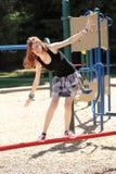Young teen girl balancing on red bar royalty free stock image