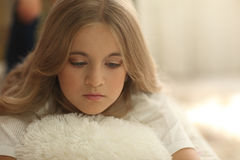 Young teen girl on bed white pillow at home, long fair hair and perfect child face.  royalty free stock image