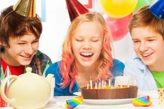 Young teen girl blow candles with friends laugh Stock Photography
