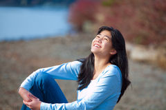 Young teen girl in blue shirt and jeans laughing along rocky lake shore Stock Image