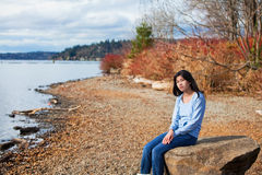 Young teen girl in blue shirt and jeans sitting along rocky lake shore Royalty Free Stock Photography