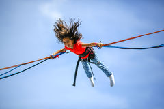 Young teen girl in bungee jumping trampoline Stock Images