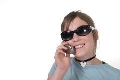 Young Teen Girl With Cellphone 7a. Cute tween or young teenage girl wearing sunglasses and talking on a cellphone; shot on white Royalty Free Stock Image
