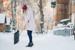 Young teen girl cleans snow near the house, holding a shovel and paddle spend time Stock Image