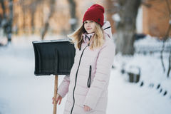 Young teen girl cleans snow near the house, holding a shovel and paddle spend time Royalty Free Stock Photo