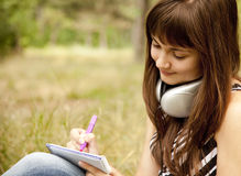 Young teen girl doing homework at the park Stock Photography