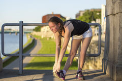 Young teen girl doing warm-up exercises before a run. Stock Photo