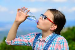 Young girl drinking water outdoors Stock Photos