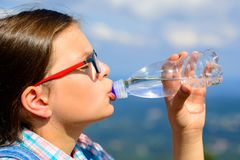 Young girl drinking water outdoors Royalty Free Stock Image