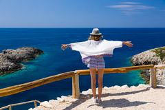 Young teen girl enjoys the wind, sunshine and view, at the edge of a high cliff over the blue sea of Greece. royalty free stock photos