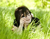 Young teen girl in glasses at green grass Royalty Free Stock Photography