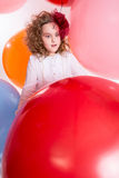 Young teen girl in a hat and white dress on a background of big. Colored rubber air balls. Cheerful girl looks at the big red ball Royalty Free Stock Photo