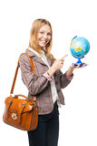 Young teen girl holding globe and pointing at it Royalty Free Stock Image