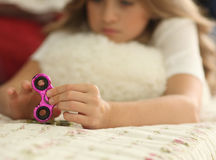 Young teen girl holding popular fidget spinner toy - closeup shot of spinner, home interior Royalty Free Stock Photo