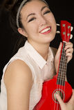 Young teen girl holding a red ukulele smiling Royalty Free Stock Photo