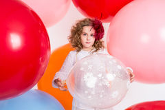 Young Teen Girl In A Hat And White Dress On A Background Of Large Air Rubber Balls Royalty Free Stock Images