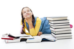 Young teen girl lay with many books stock photos