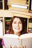 Young teen girl in library among books emotional Royalty Free Stock Photos