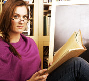 Young teen girl in library among books emotional Stock Image