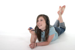 Young Teen Girl Listening To Music 1. Cute, smiling, young teenage girl lying on the floor and listening to music with headphones and mp3 player; shot on white Royalty Free Stock Images