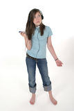 Young Teen Girl Listening To Music 2. Cute young teenage girl standing and listening to music with headphones and mp3 player; shot on white Stock Photo