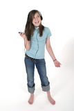 Young Teen Girl Listening To Music 3. Cute, smiling, young teenage girl standing and listening to music with headphones and mp3 player; shot on white Stock Photos