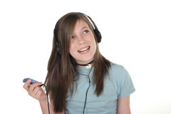 Young Teen Girl Listening To Music 4. Cute, smiling, young teenage girl standing and listening to music with headphones and mp3 player; shot on white Royalty Free Stock Image