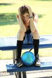 Young teen girl looking sad with soccer ball. Young teen girl sitting on table holding head with soccer ball looking distraught Royalty Free Stock Photo