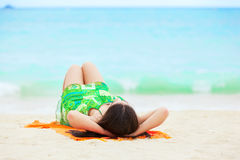 Young teen girl lying on back at tropical beach Royalty Free Stock Photos