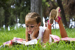 Young teen girl lying on green grass and reading book stock photos