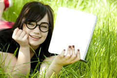 Young teen girl with notebook at green grass Stock Photography
