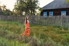 A young woman in an old-fashioned vintage sarafan dress is walking along the fence of a rustic abandoned wooden house. A young teen girl in an old-fashioned stock photo