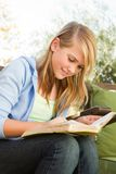 Young teen girl outside reading. Young teen girl outside reading in the backyard royalty free stock photography