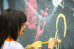 Young teen girl paints the  wall Stock Image