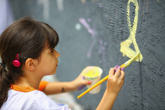 Young teen girl paints the wall stock images